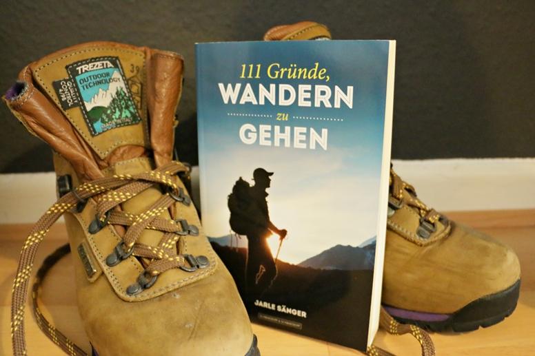 Titelbild von dem Buch 111 Gründe, wandern zu gehen mit Wanderschuhen im Hintergrund